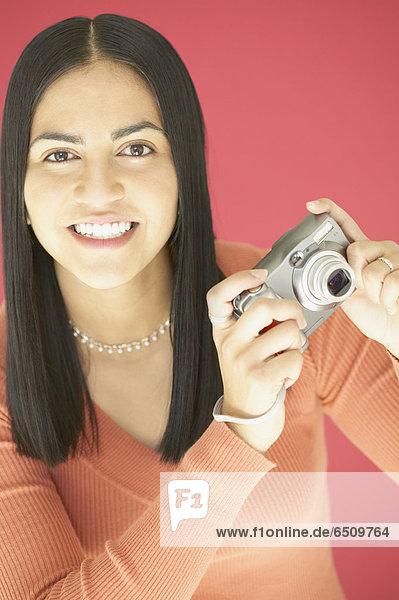 junge Frau hält eine Kamera