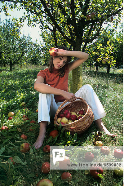 Young woman with apples in the garden.
