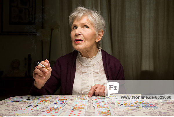 Old lady smoking cigarette while telling fortunes by cards