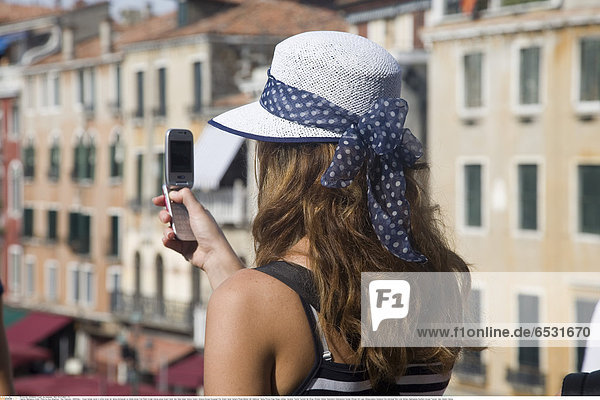 Mandatory Credit: Photo by Eye Ubiquitous / Rex Features ( 1269364a ) Young female tourist in white straw hat taking photograph on mobile phone from Rialto bridge looking along Grand Canal. Italy Italia Italian Venice Veneto Venezia Europe European City Grand Canal Camera Phone Mobile Cell Cellphone Taking Picture Snap Snaps Holiday Vacation Tourist Tourists Hat Straw Woman Cellular Destination Destinations Female Women Girl Lady Holidaymakers Immature One individual Solo Lone Solitary Sightseeing Southern Europe Tourism Italy Veneto Venice