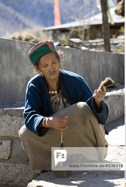 Mandatory Credit: Photo by Phil Clarke-Hill / SpecialistStock / Rex Features ( 1277401a ) traditionally dressed elderly Kinnauri Buddhist Indian woman concentrating on spinning yarn  Chitkul  Kinnaur valley / district  Himachal Pradesh  Himalayas  India VARIOUS