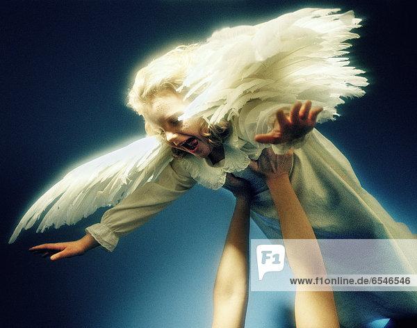 Child wearing angel costume holding aloft