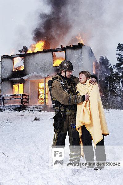 Feuerwehrmann Senior Senioren Rettung verbrennen Frau Wohnhaus frontal
