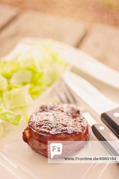 Gegrillter Speck mit Salat auf dem Teller