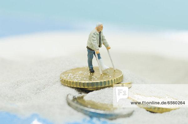 Figuren eines behinderten Patienten am Strand mit Euro-Münze
