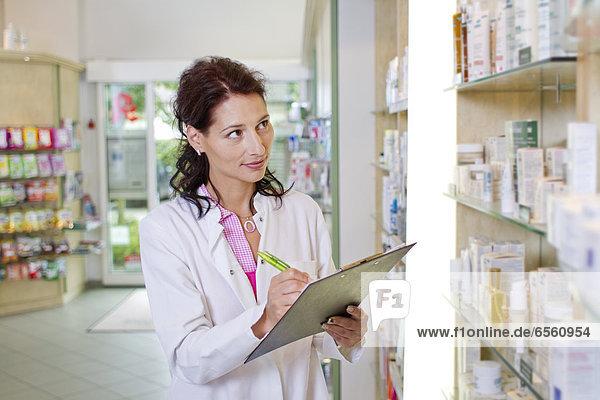 Germany  Brandenburg  Pharmacist checking products in pharmacy