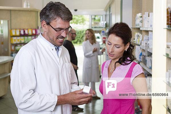 Apothekerin zeigt Frau Medizin