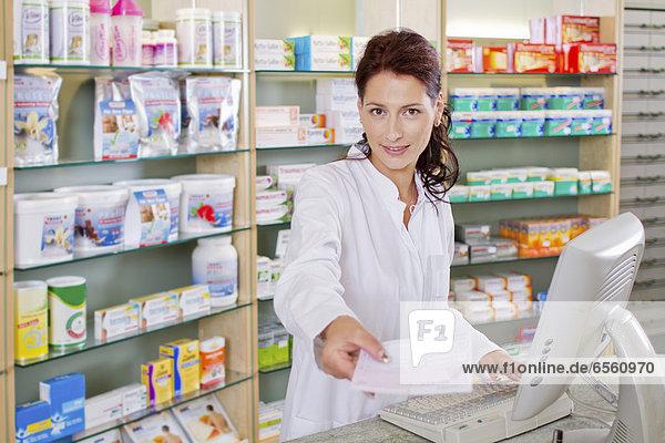 Germany  Brandenburg  Pharmacist holding prescription  smiling  portrait