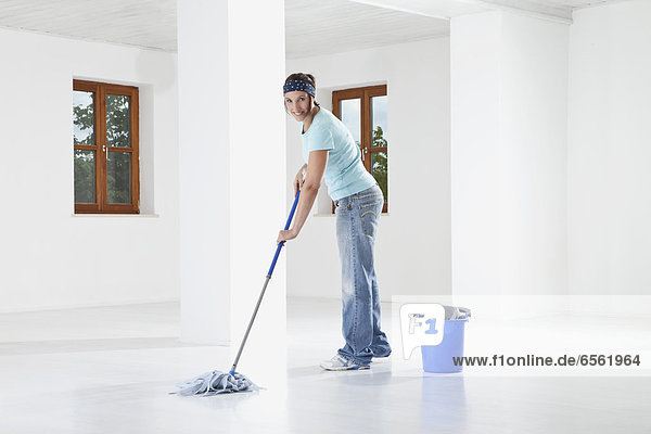 Young woman mopping floor  smiling  portrait