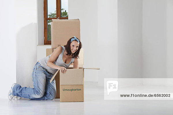 Young woman packing cardboard box  smiling  portrait