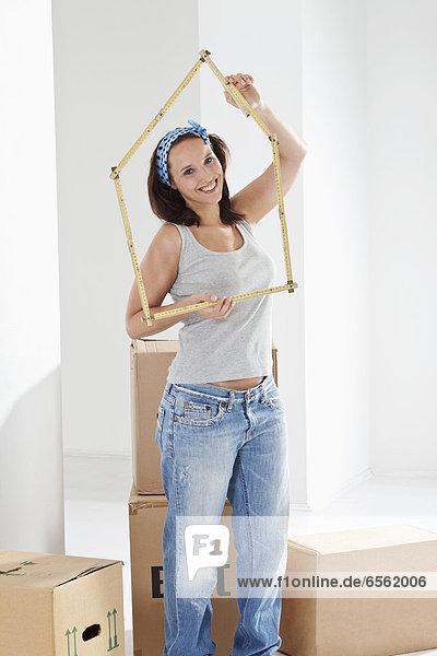 Junge Frau macht Hausform mit Zollstock  lächelnd  Portrait