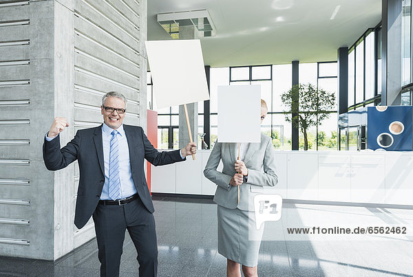 Germany  Stuttgart  Business people holding blank signs in office lobby  smiling