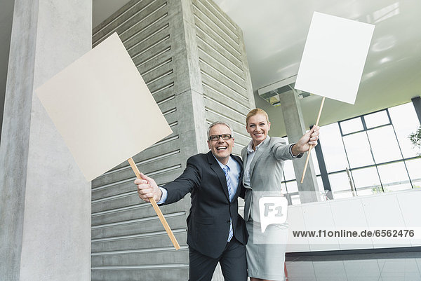 Germany  Stuttgart  Business people holding blank signs in office lobby  smiling  portrait