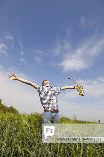 Teenage boy stretching arms and holding saxophone in nature