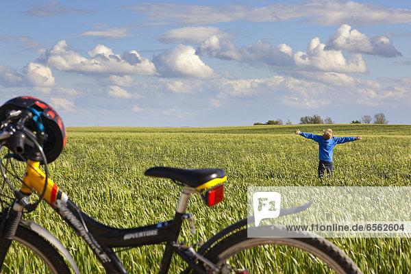 Junge steht und streckt Arme im Feld  Fahrrad im Vordergrund