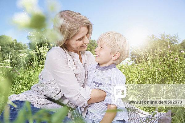 Deutschland  Köln  Mutter und Sohn beim Picknick auf der Decke sitzend