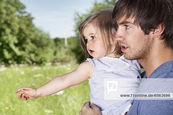 Deutschland  Köln  Vater und Tochter auf der Wiese