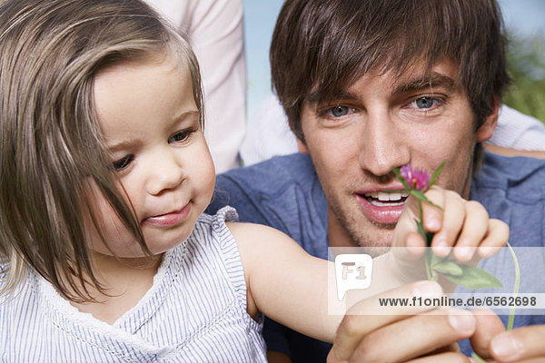 Girl holding flower with parents  close up