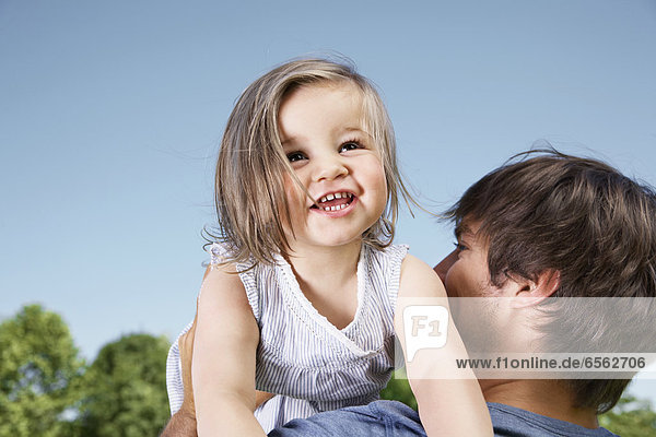 Germany  Cologne  Father holding her daughter  smiling