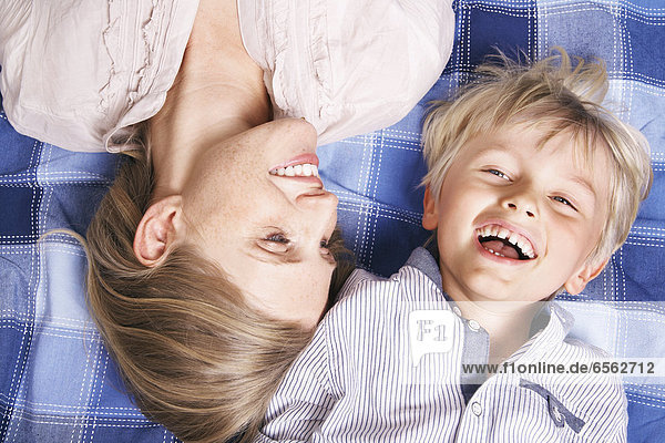 Germany  Cologne  Mother and son lying on blanket  smiling