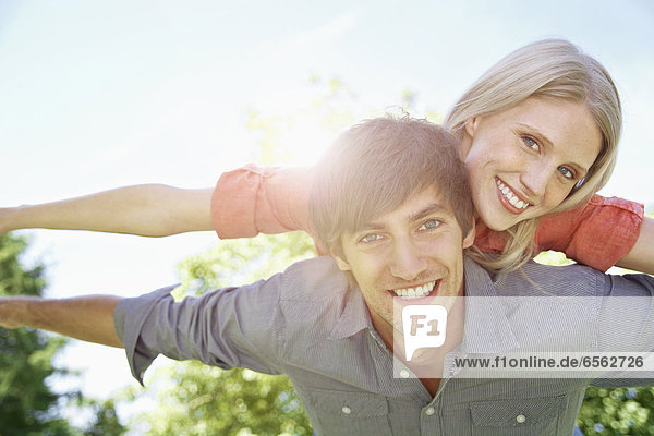 Germany  Cologne  Young couple flying  smiling  portrait