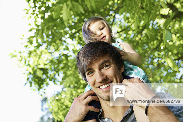 Germany  Cologne  Father carrying daughter on shoulders  smiling