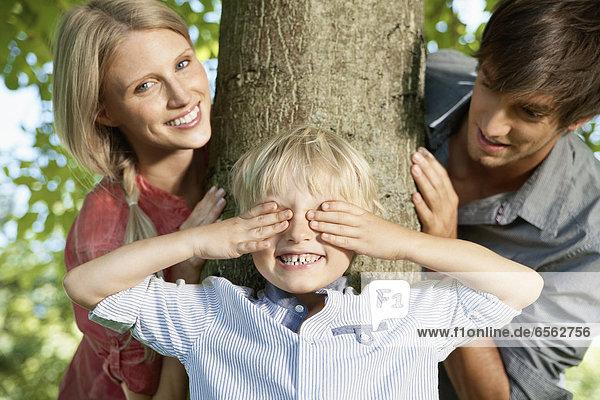 Junge spielt Verstecken mit den Eltern.
