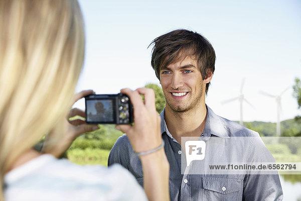 Junge Frau beim Fotografieren des Mannes