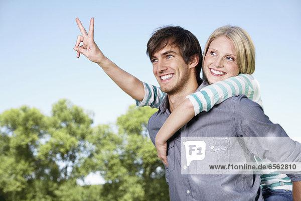 Deutschland  Köln  Junges Paar umarmt  zeigt Friedenszeichen
