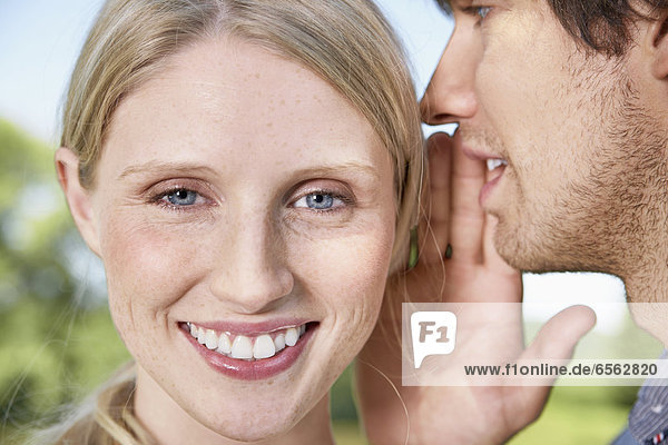 Junger Mann flüstert zur Frau