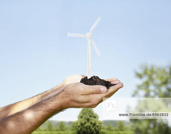 Junger Mann hält Windkraftanlage mit Erde