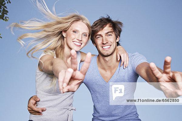 Deutschland  Köln  Junges Paar mit Friedenszeichen  lächelnd  Portrait