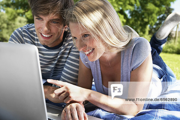 Germany  Cologne  Young couple using laptop in meadow  smiling