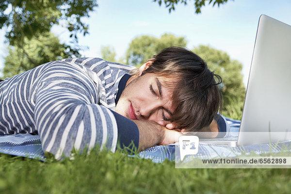 Junger Mann schläft auf der Wiese