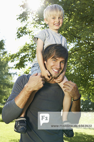 Germany  Cologne  Father carrying son on shoulders  smiling  portrait