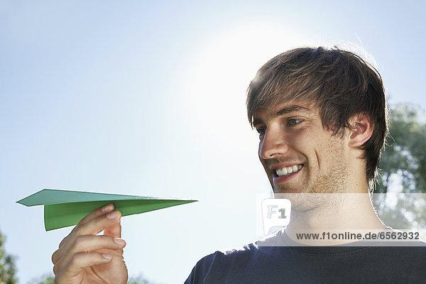 Junger Mann mit Papierflieger