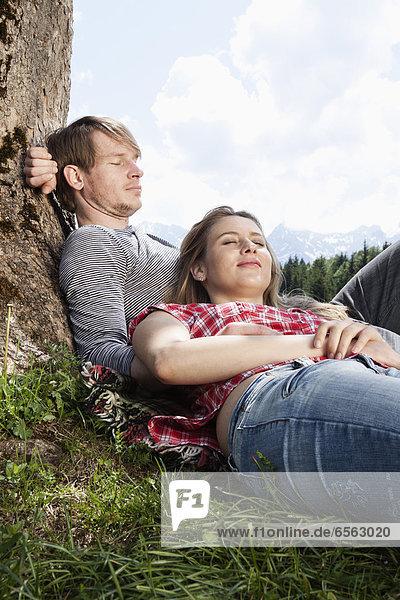 Deutschland  Bayern  Pärchen entspannen unterm Baum