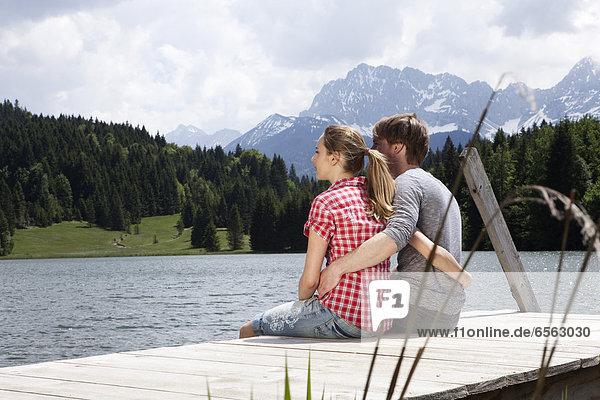 Deutschland  Bayern  Paar am Steg sitzend und mit Blick auf die Aussicht