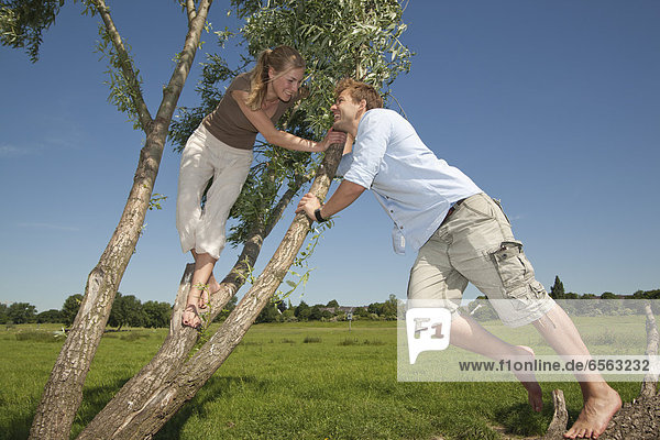 Germany  North Rhine Westphalia  Duesseldorf  Couple playing with tree  smiling