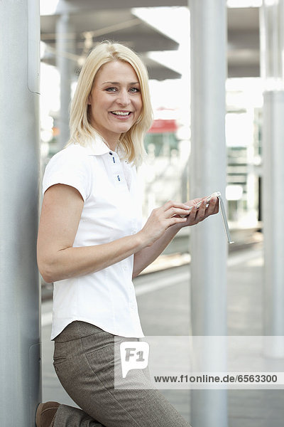 Mid adult woman standing with smartphone