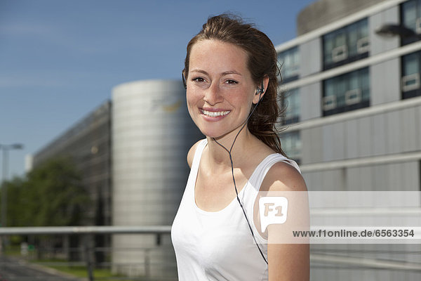Young woman listening head phones  smiling  portrait