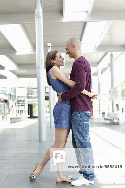 Junge Frau  die sich im Bahnhof umarmt.