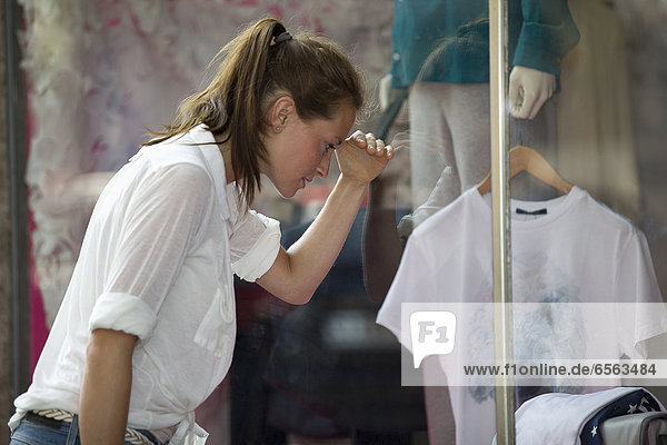Germany  North Rhine Westphalia  Cologne  Young woman at window shopping