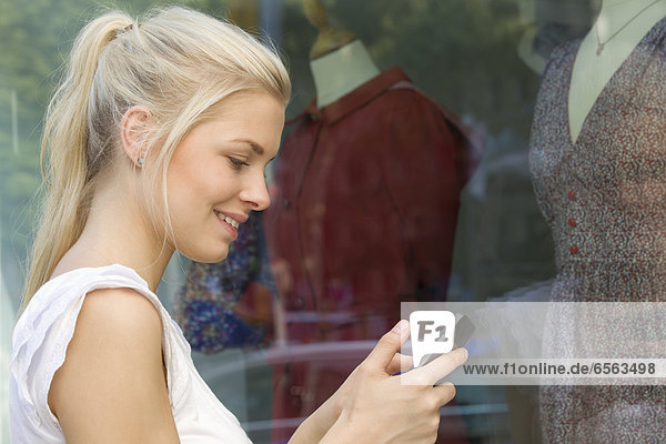 Germany  North Rhine Westphalia  Cologne  Young woman at window shopping with smart phone