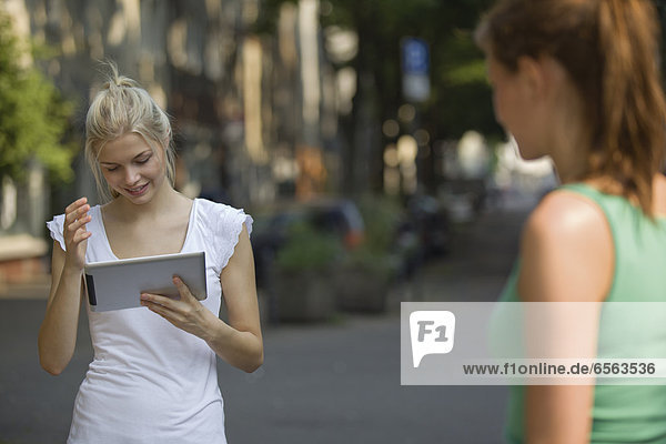 Germany  North Rhine Westphalia  Cologne  Young women with digital tablet on street  smiling