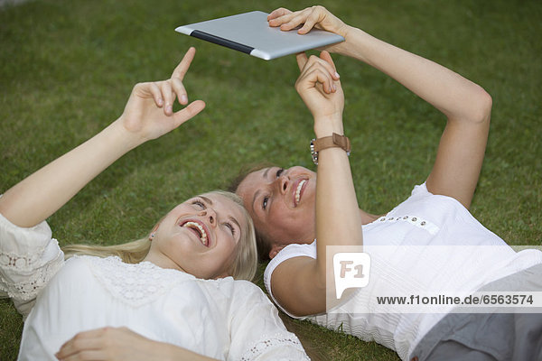 Germany  North Rhine Westphalia  Cologne  Young students using digital tablet  smiling