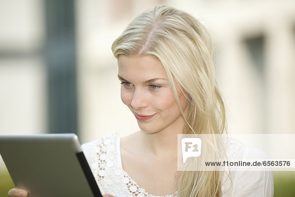 Germany  North Rhine Westphalia  Cologne  Young student with digital tablet  smiling