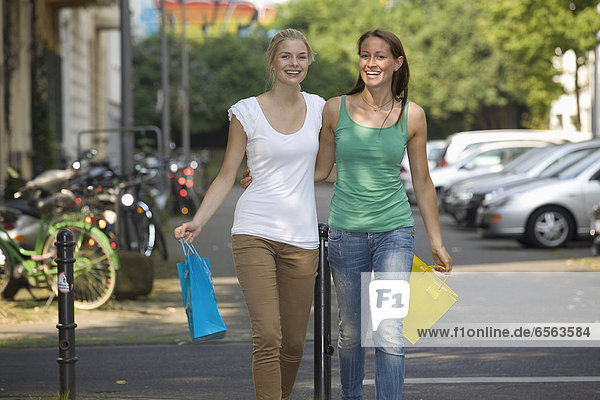 Germany  North Rhine Westphalia  Cologne  Young women with shopping bags on street  smiling