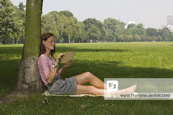 Germany  North Rhine Westphalia  Cologne  Young student sitting in park with digital tablet  smiling
