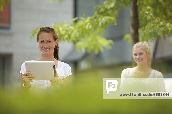 Germany  North Rhine Westphalia  Cologne  Young woman with digital tablet  smiling